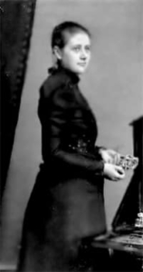 A black and white image of a woman wearing a black dress