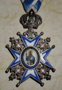A colour photograph of an ornate iron medal with blue decoration