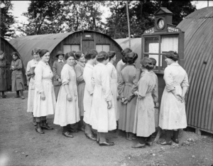 A black and white photograph of a group of nurses wearing uniform gathered outside corrugated iron huts