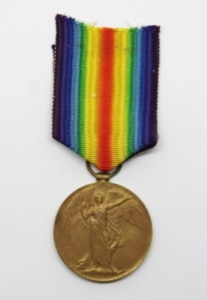 A colour photograph of a bronze medal with a winged figure engraved on it, attached to a rainbow ribbon