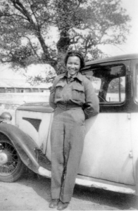 A black and white photograph of a young Lilian Bader leaning on a car