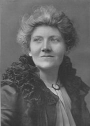 A black and white photograph of a woman with short light brown curly hair, looking triumphant
