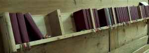A colour photograph of a long church shelf full of hymn books.