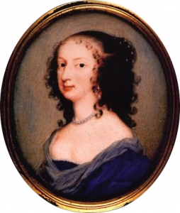 A colour image of a portrait of a young woman with long black curly hair, wearing a blue dress and a pearl necklace