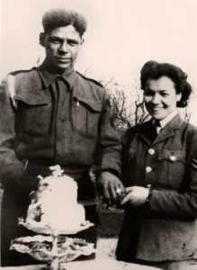 A black and white photograph of Lilian Bader and her husband Ramsay Bader cutting their artificial wartime wedding cake