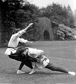 Black and white photograph of Mary Bedford sparring with another woman during jujitsu practice, on a lawn