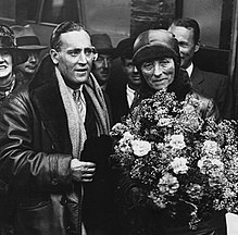 A black and white photo of Mary Russell standing with her pilot C D Barnard and holding a large bunch of flowers