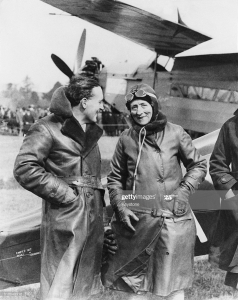 A black and white photo of Mary Russell wearing a leather aviator jacket and goggles, standing in front of a plane chatting and smiling with another man, also wearing a leather aviator jacket