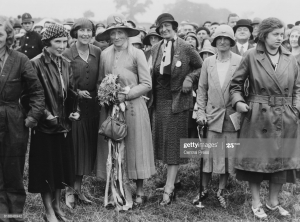 A black and white image of seven women wearing 1930s coats and hats, standing in a field with a large crowd