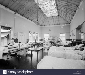 A black and white image of a hospital ward, filled with metal bedframes, patients and nurses and a high ceiling with a bright skylight