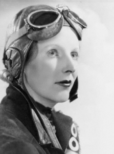 A black and white profile photograph of a woman with aviator goggles on her head