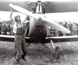 A black and white photograph of aircraft engineer turning the propellor of a small aircraft with a crowd of onlookers