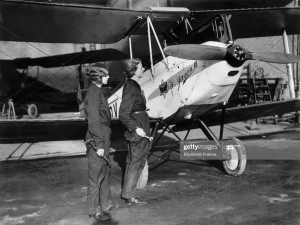 A black and white image of two women in engineer's boiler suits standing by a small aircraft and looking at the propellor