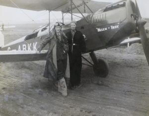 "A black and white photograph of two women in pilot uniforms standing by the cockpit of a plane with the name ""Helen of Troy"""