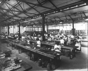 A black and white historical photograph of women working at long desks on radios in a large warehouse