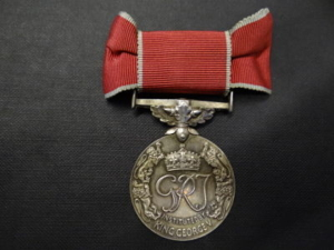 A colour photograph of a silver medal with red ribbon