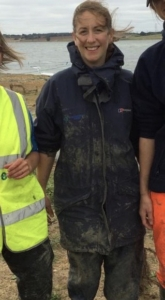 A colour photograph of a scientist at the beach on a windy day, wearing muddy outdoor clothing and flanked by two other scientists