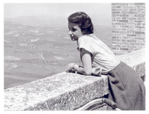 A black and white photo of a woman looking out across an italian landscape