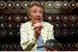 A colour photograph of a woman holding a circular section of a bombe machine, with her hand raised and explaining how it works