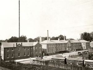 A black and white historical photograph of a set of long buildings