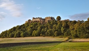 A colour photograh of a castle on a a hill covered in woodland and bathed in sunlight