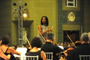 A colour photograph of a woman conducting an orchestra