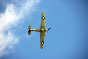 A colour photograph of an old khaki aeroplane in the sky viewed from below