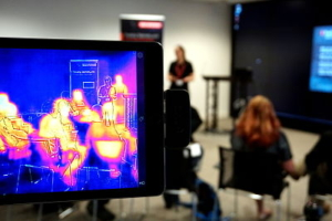 A colour photograph of an infrared camera taking a video of a woman doing a scientific presentation