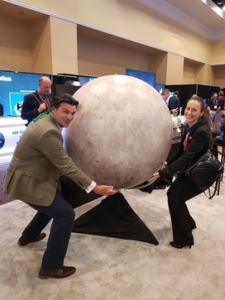 A colour photograph of a woman and man at a scientific convention holding a large spherical stone ball
