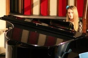 A colour photo of a woman playing a grand piano