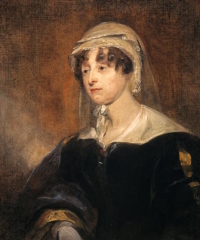 A colour portrait of a woman with brown curly hair wearing a black coat and a white bonnet with a veil