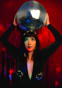 A colour photograph of a woman dressed in a sparkly black outfit in front of a red glittery background holding a disco ball on her head