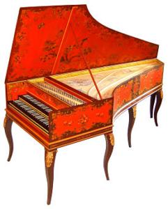 A colour image of a bright orange double-manual harpsichord