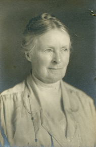 An old portrait photograph in sepia of a woman with her hair tied into a bun, wearing a cream-coloured blazer