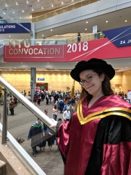 A colour photograph of a woman standing on some steps in a university foyer with the sign 'convocation 2018' in the background. She has brown hair and is wearing glasses, a black graduation gown with red and gold silk and a black graduation cap.