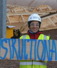 A colour photograph of a woman wearing a hard hat an high-vis jacket holding a sign labelled 'Constructiona'