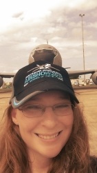 A colour photograph of a woman wearing a baseball cap in front of an aeroplane and smiling