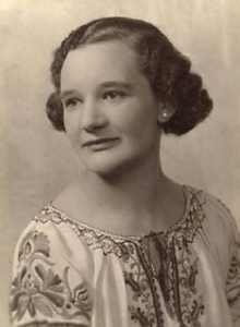 An old sepia photograph of a woman. She has short brown hair in an early 20th-century (1920s) curled style. She is wearing pearl earrings and a flowy white top with embroidered floral print and a string bow tied at the top - in a 'folk' style. She looks defiant, gazing slightly to the right of the camera.