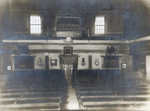 An old black and white photograph of an interior of a central london style chapel, with a balcony surrounding the floor-level pews and an organ at the top in the centre