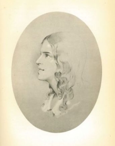 A sepia drawing of a woman's face, in an oval frame on a cream paper background. The face is in portrait position, and she is looking away from the viewer, towards her right. She has mid-length curly brown hair and is wearing a white collared shirt.