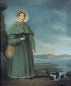 A colour portrait of a woman wearing a green dress in a 19th-century style, a straw bonnet with a red ribbon, a straw basket and a pickaxe. She is standing at the seashore and her left arm is pointing downwards at a large rock and a black-and-white dog asleep next to it. The sky is grey and stormy, with sunny skies visible in the distance.