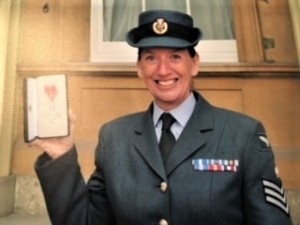 A colour photograph of a woman wearing navy blue RAF uniform smiling and holding a small, open, notebook. Her uniform consists of a blue blazer with 3 chevrons embellished on the arm, a series of badges on her left breast, and a narrow-brimmed hat in the same blue material with a black band and a gold RAF sigil. She is also wearing a shirt and tie, and is standing in front of the window of a gold stone building.