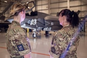 A colour photograph of two women in camo RAF uniforms standing in an aircraft hanger. They are looking away from the camera, towards a large fighter jet in the backgruond.