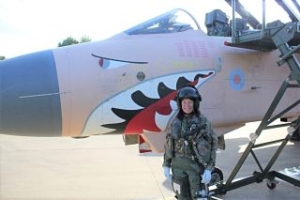 A colour photograph of a woman standing in a pilot's uniform in front of a fighter jet with a novelty design on its nose. The jet is painted with a peach-coloured shark's face.