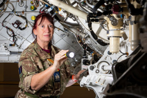 A colour photograph of a woman wearing camo RAF uniform, surrounded by complicated machinery in what looks like the inside of an aircraft. She is pointing a lit torch at some of the machinery and is looking slightly away from the camera. She has dark red hair tied into a ponytail.