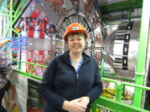 A colour photograph of a woman wearing a navy zip-up fleece and an orange hard-hat, standing in front of the Large Hadron Collider. She is leaning against the fence of a high walkway, which consists of a metal frame and is painted bright green. Behind her, the collider is mostly silver metal, full of complex wiring and panels. There is a big circular panel on the wall, attached to the start of a large, horizontal, cyndrical object, also silver.