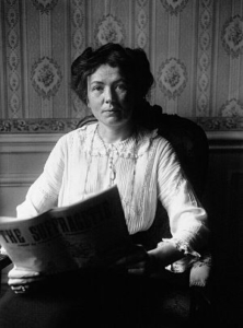 A black and white photograph of a woman sitting in an armchair holding a newspaper. She is looking directly into the camera. She is wearing a white lacy collared shirt and has dark hair, tied into a bun. She also has reading glasses hanging around her neck. Behind her, there is a wall with ornately patterned wallpaper.