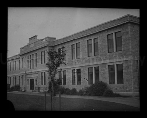 A black and white photograph of a large brick building with two floors and a long string of 10-15 windows along the front. The building looks like a university campus or a school.