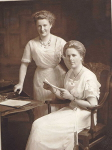 A sepia photograph of two young women wearing long white dresses. They both have brown hair in updos. One is sitting at a chair holding some paperwork, and the other is standing behind with her hand on the chair