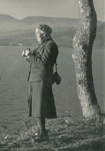 A black and white photograph of an old woman wearing a dark skirt and blazer, looking out over a magnificent loch and holding a pair of binoculars